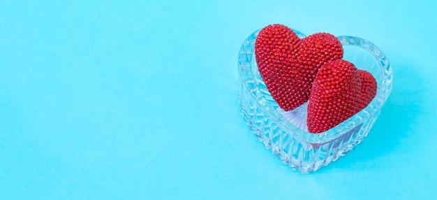 Valentinstag. rotes herz auf den blauen brettern. valentinstag. herzanhänger. rotes herz. platz für text.