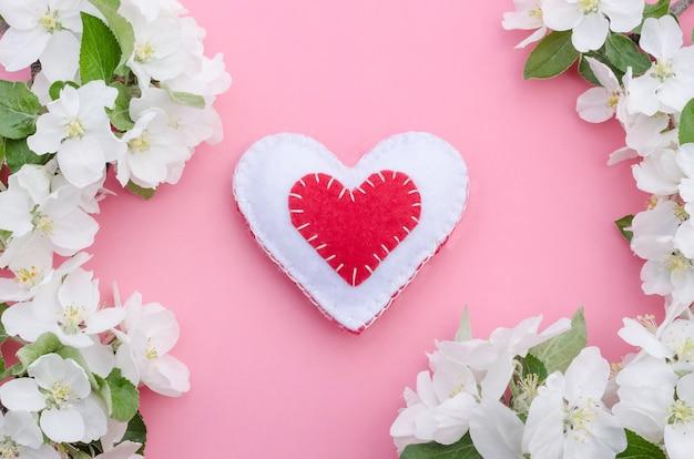 Valentinstag, rotes und weißes handgemachtes herz mit apfelbaumblumenrahmen auf rosa hintergrund
