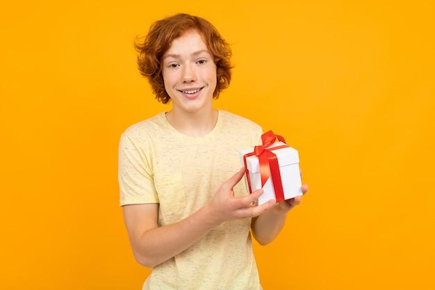 Valentinstag . rothaariger jugendlicher mit einem geschenk in seinen händen auf einem gelb