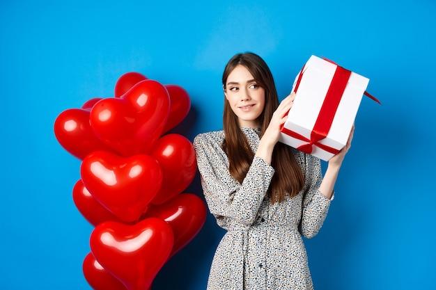 Valentinstag schöne frau, die geschenkbox schüttelt, um zu erraten, was drinnen liebhaber feiert ...