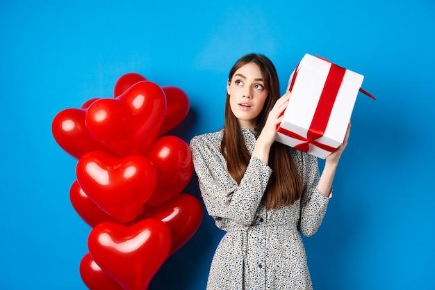 Valentinstag schöne frau, die geschenkbox schüttelt, um zu erraten, was innen verträumt aussieht und liebhaber feiert ...