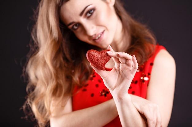 Valentinstag. schöne junge frau mit herz in ihren händen. junge frau mit rotem herzen auf schwarzem hintergrund. porträt der attraktiven lächelnden frau studio mit herzen geschossen. nahansicht