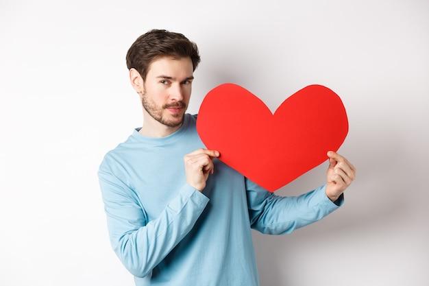 Valentinstag. schöner und romantischer mann, der einen großen roten valentinstag-herzausschnitt hält, verführerisch in die kamera schaut, liebesgeständnis macht, weißer hintergrund.