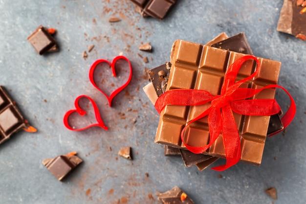 Valentinstag. schokoriegel verziert rotes band und herzen. draufsicht