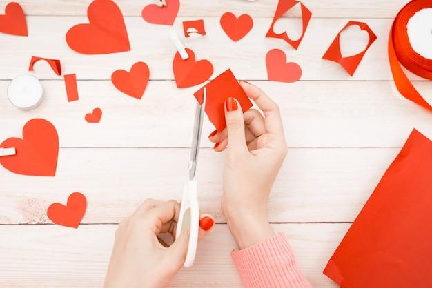 Valentinstag scrapbook, hochzeit oder andere feiertagsdekorationen hintergrund. handgemachtes geschenkgrußherz, das herstellt, ausschneidet und einfügt, bastelpapier und diy-werkzeuge auf weißem holz. ansicht von oben, flach