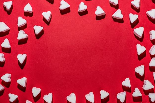 Valentinstag süßigkeiten herzen marshmallows auf rotem hintergrund