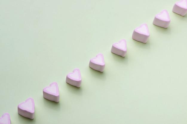 Valentinstag süßigkeiten herzen marshmallows über grünem hintergrund
