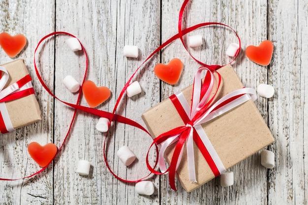 Valentinstag süßigkeiten herzen marshmallows und schachtel mit geschenken in bastelpapier über weißem holzhintergrund.