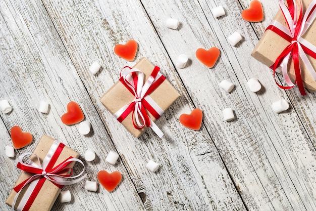 Valentinstag süßigkeiten herzen marshmallows und schachtel mit geschenken in bastelpapier