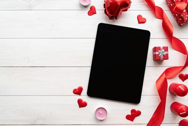 Valentinstag. tablette mit schwarzem bildschirm mit valentinsdekorationskerzen, luftballons und konfetti-draufsicht auf weißem hölzernem hintergrund