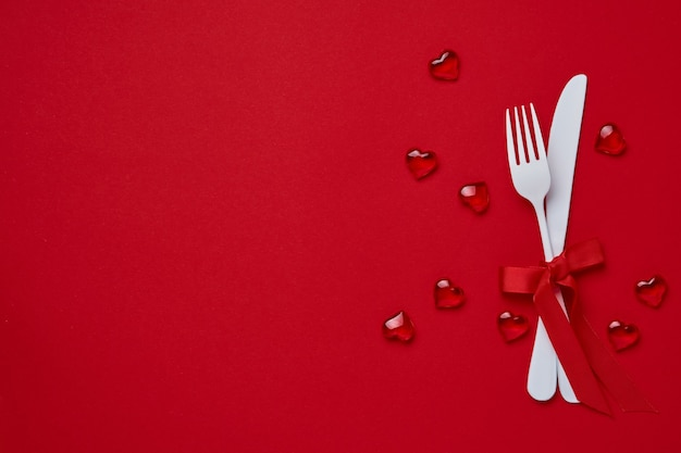 Valentinstag tisch oder konzept mit leerem weißen teller, kleiner herzförmiger teller mit kleinen herzen im inneren und whiteware auf scharlachrotem oder rotem tisch. . draufsicht mit kopierraum.