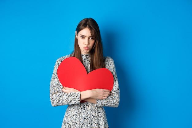 Valentinstag trauriges und düsteres kaukasisches mädchen verzieht die lippen und sieht enttäuscht aus, hält großes rotes...