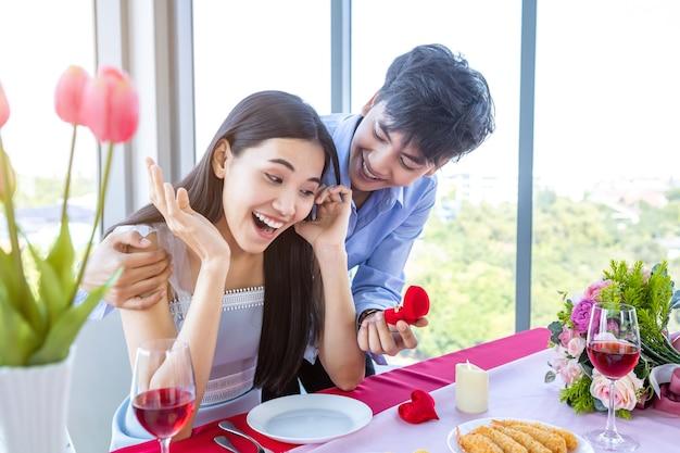 Valentinstag und asiatisches junges glückliches süßes paarkonzept, asiatischer mann mit verlobungsring, der der frau nach dem mittagessen einen heiratsantrag macht in einem restauranthintergrund, hochzeitspläne für braut und bräutigam