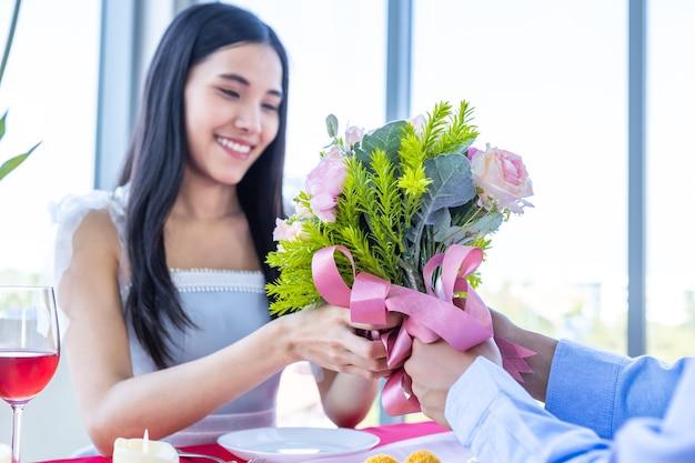 Valentinstag und asiatisches konzept des jungen glücklichen paares, ein mann, der einen blumenstrauß rosen hält geben sie der frau mit den händen über das lächeln ihres gesichtes erwartet überraschung nach dem mittagessen in einem restauranthintergrund