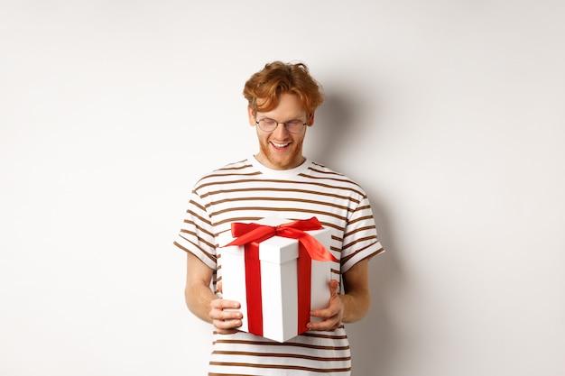 Valentinstag und feiertagskonzept. glücklicher bärtiger kerl, der sein geschenk hält und lächelt, kasten mit geschenk innen betrachtend, über weißem hintergrund stehend.