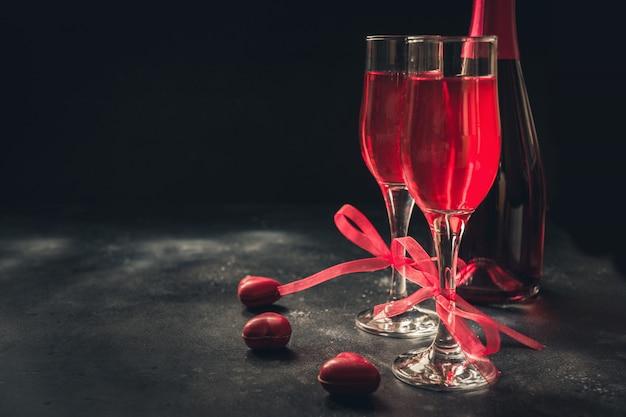 Valentinstag- und geburtstagsgrußkarte mit champagner- und herzsüßigkeit auf schwarzem.