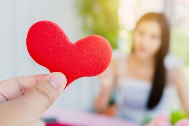 Valentinstag und junges glückliches paarkonzept, nahaufnahme des mannes, der small ein rotes herz über ihrem gesicht weiblich hält, erwartet überraschung nach dem mittagessen in einem restaurant