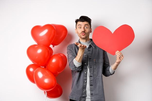 Valentinstag und liebeskonzept. romantischer junge, der herzkarte zeigt und luftkuss an der kamera bläst, mit sympathie auf liebhaber schaut, weißen tag feiert.