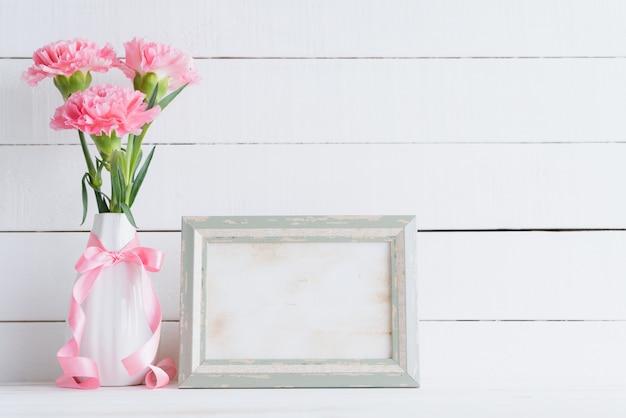 Valentinstag und liebeskonzept. rosa gartennelke im vase auf hölzernem hintergrund.