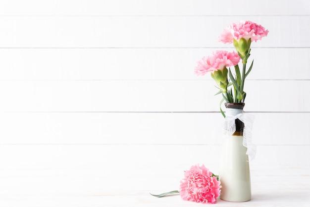 Valentinstag und liebeskonzept. rosa gartennelkenblume im vase auf hölzernem.