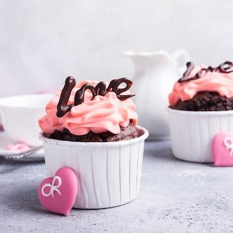 Valentinstag und muttertag, hochzeitsgrußkarte mit schönem schokoladencupcake, rosa creme und herz auf grauer steinoberfläche mit kopienraum
