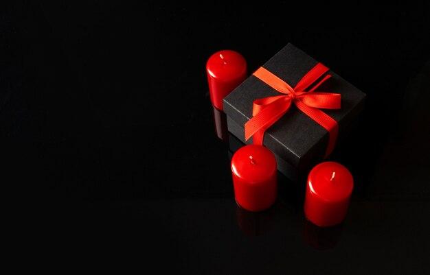 Valentinstag urlaub hintergrund mit einer schwarzen geschenkbox und roten kerzen.