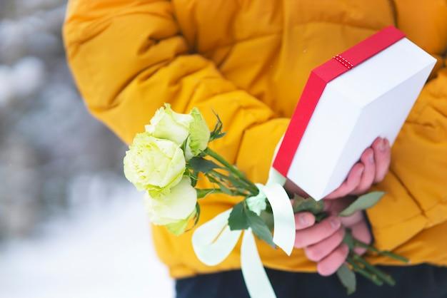 Valentinstag urlaub. junger mann kerl hält ein geschenk und einen nahaufnahmestrauß von rosen, blumen geschenkbox, hinter seinem rücken.