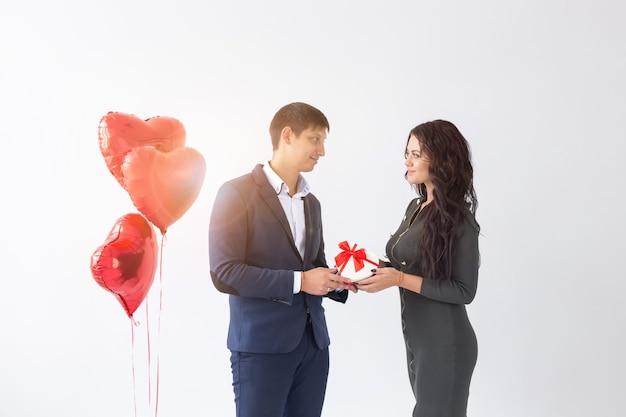 Valentinstag, urlaub und geschenkkonzept. glückliches junges paar mit valentinstaggeschenk isoliert auf weißem hintergrund. glücklicher mann, der seiner freundin ein geschenk gibt.