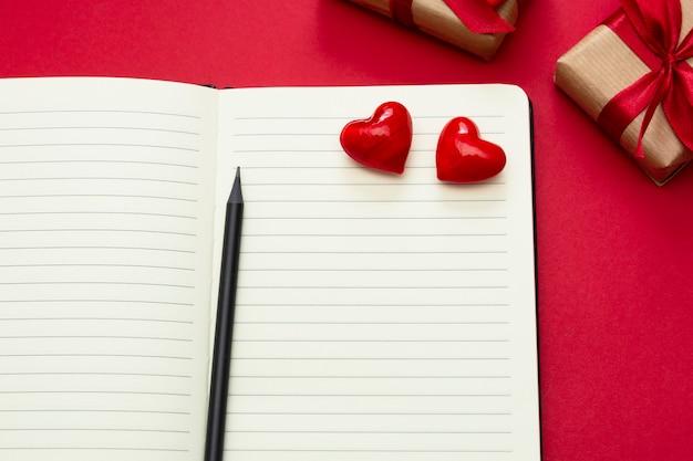 Valentinstag verspotten. öffnen sie notizbuch mit roten herzen und geschenkboxen, auf rotem hintergrund, kopienraum für text.