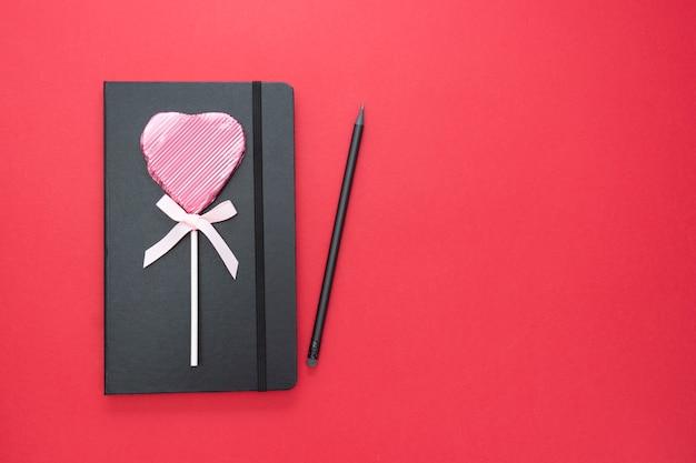 Valentinstag-vorlage. schwarzes notizbuch auf rotem hintergrund mit einem herzen formte lutscher- und kopienraum.