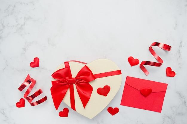 Valentinstag wand draufsicht. geschenkbox in form eines herzens mit einer roten schleife, herzen, band auf einem weißen tisch.