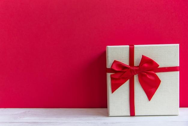 Valentinstag weiße geschenkbox mit einem roten bogen auf rotem wandhintergrund, kopienraum. valentine-konzept.