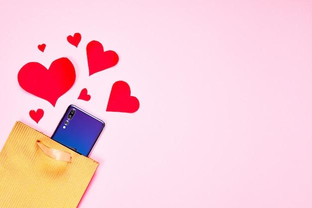 Valentinstag wohnung lag kopierraum. goldene papiergeschenktüte, smartphone und rote herzen auf rosa papierhintergrund.