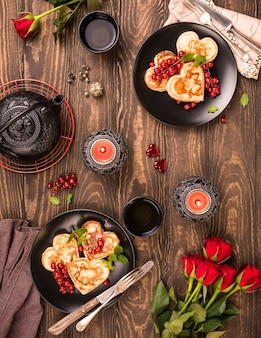 Valentinstag wohnung lag mit leckeren pfannkuchen in form von herz, grünem tee, schwarzer teekanne, kerzen und rosen. valentinstag konzept grußkarte. draufsicht