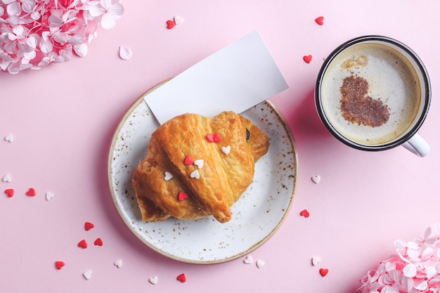 Valentinstag wohnung lag mit zwei tassen kaffee, croissant auf teller auf rosa