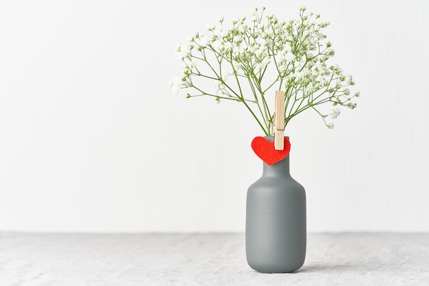 Valentinstag. zarte weiße blüten in einer vase. rotes filzherz - symbol der liebenden