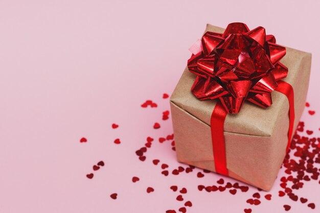 Valentinstag zusammensetzung: geschenkbox mit roter schleife und roten herzen form glühenden konfetti, auf rosa pastell hintergrund.
