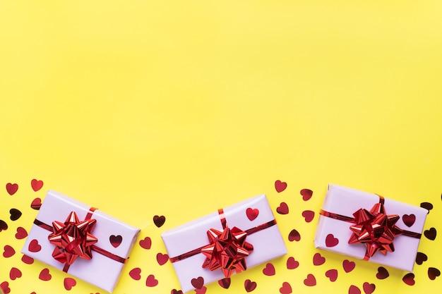 Valentinstag zusammensetzung, gruß geschenkbox mit konfetti herzen auf gelbem hintergrund. flach liegen.