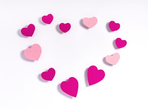 Valentinstag zusammensetzung. herzform gemacht von den purpurroten und rosa papierherzen auf weißbuch. valentinstag . flache lage, draufsicht, copyspace