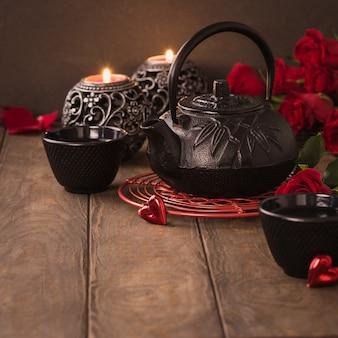 Valentinstag zusammensetzung mit grünem tee, schwarzer teekanne, kerzen und rosen auf holztisch. valentinstag grußkartenkonzept mit kopienraum
