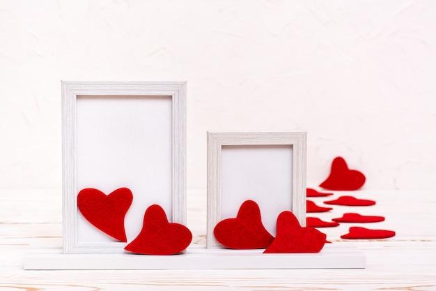 Valentinstag. zwei leere weiße rahmen, umgeben von roten filzherzen. speicherplatz kopieren