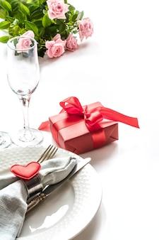 Valentinstagabendessen mit tabellengedeck mit rotem geschenk, glas für champagner. valentinstagskarte.