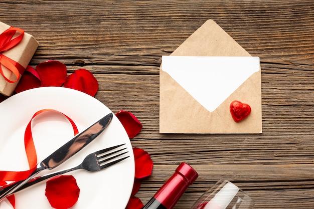 Valentinstagabendessenzusammenstellung mit leerem umschlag