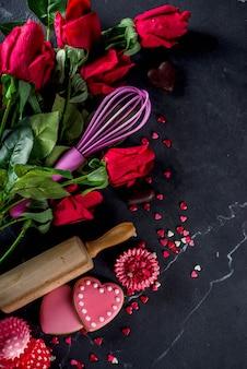 Valentinstagbackenhintergrund mit rosen und backenwerkzeugen