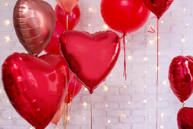 Valentinstagdekoration - gruppe rote herzförmige ballons über weißem wandhintergrund