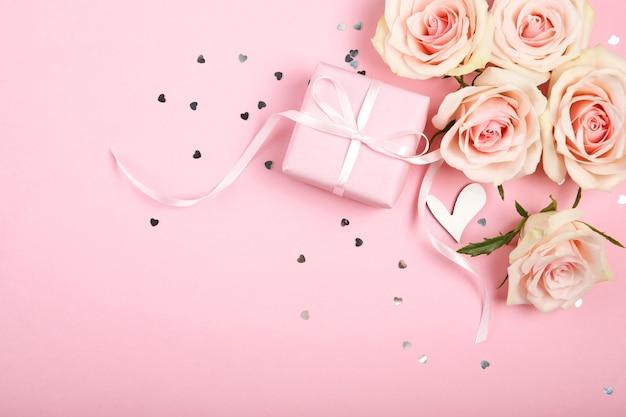 Valentinstagdekorationen, blumenstrauß und geschenk auf rosa hintergrund
