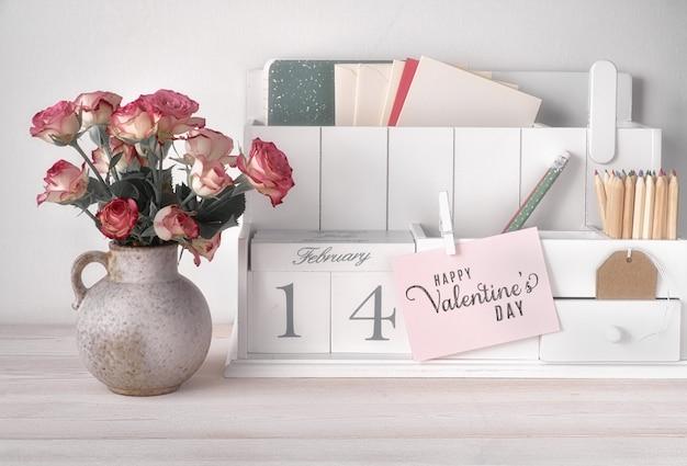 Valentinstagdekorationen, weißer schreibtischorganisator mit holzkalender, tasse heißer schokolade und rosa rosen.
