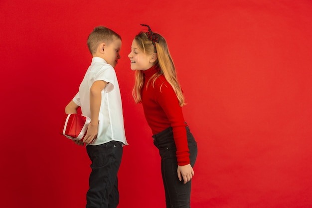 Valentinstagfeier, glückliche, niedliche kaukasische kinder lokalisiert auf rotem studio