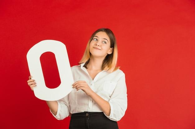 Valentinstagfeier, glückliches kaukasisches mädchen, das brief auf rotem hintergrund hält