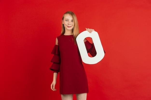 Valentinstagfeier, glückliches, niedliches kaukasisches mädchen, das brief auf rotem studiohintergrund hält.